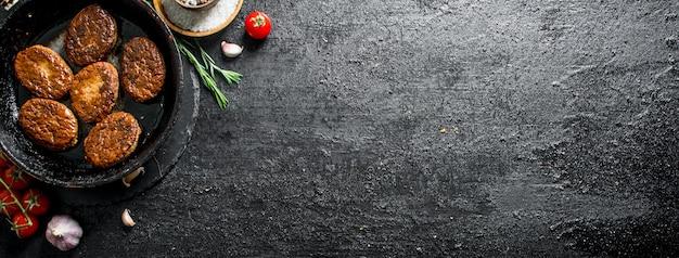 Schnitzel in einer pfanne mit rosmarin, knoblauch und tomaten. auf schwarzem rustikalem hintergrund