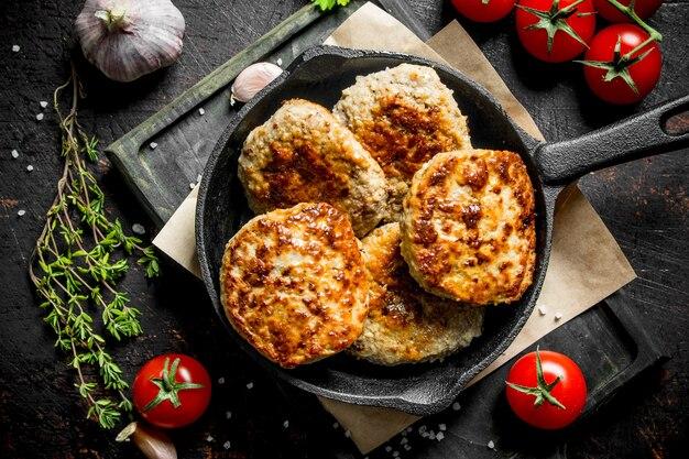 Schnitzel in einer pfanne mit thymian, knoblauch und tomaten. auf rustikalem hintergrund
