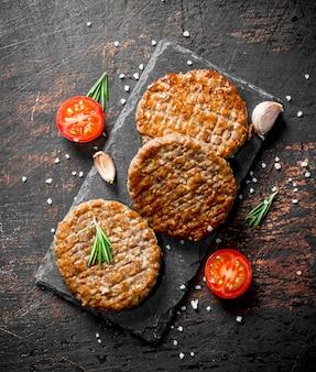 Schnitzel mit knoblauch und einer geschnittenen tomate auf dunklem holztisch