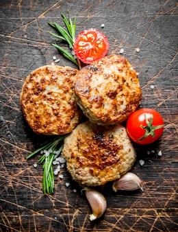 Schnitzel mit knoblauchzehen, rosmarin und tomaten. auf dunklem rustikalem hintergrund