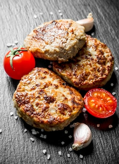 Schnitzel mit knoblauchzehen und tomaten. auf schwarzem rustikalem hintergrund