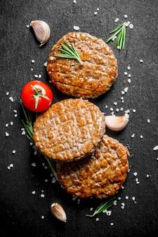 Schnitzel mit salzstücken, rosmarin und knoblauch auf dunklem rustikalem tisch