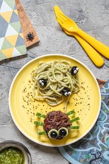 Schnitzel sehen aus wie eine spinne mit pesto-nudeln für halloween