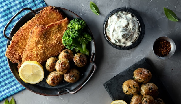Schnitzel - traditionelles österreichisches (deutsches) paniertes fleisch mit kartoffeln, sauce und gewürzen