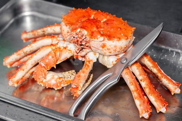 Schnitzen der frischen roten großen gekochten vorbereiteten blauen kamtschatka-krabbe mit scheren.
