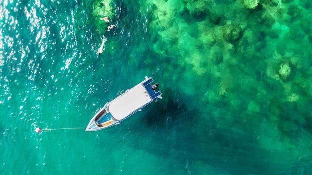 Schnorcheln in der nähe von boot in klarem tropischem meer, luftaufnahme von oben, mutter und kinder schnorchler schwimmen im wasser mit korallen in den sommerferien in thailand
