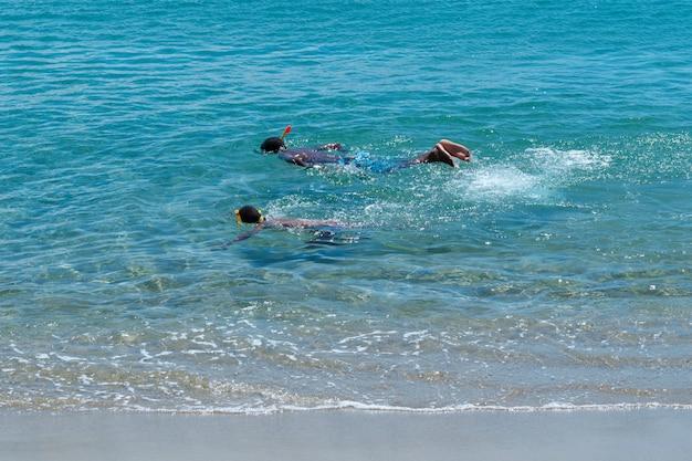 Schnorcheln von zwei schwarzen kindern im klaren meerwasser in der dominikanischen republik.