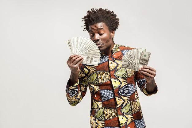 Schnüffeln sie in freude afrikanischer mann schloss die augen, die sein geld hielten