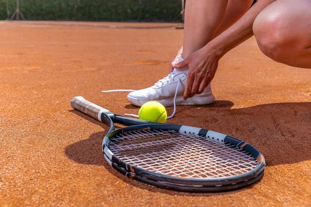 Schnürsenkel-tennisschuhe auf dem platz, schläger und ball binden.