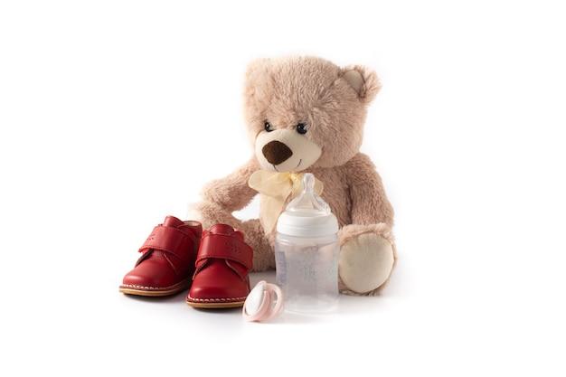 Schnullerfütterungsflasche und schuhe des teddybären isoliert