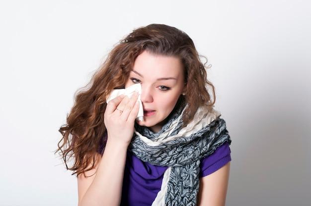 Schnupfen in einem kranken mädchen covid-19, das sitzt und weint