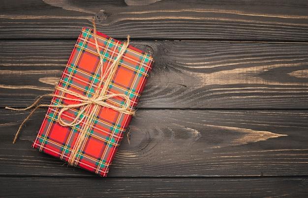 Schnur gebundenes weihnachtsgeschenk im hölzernen hintergrund