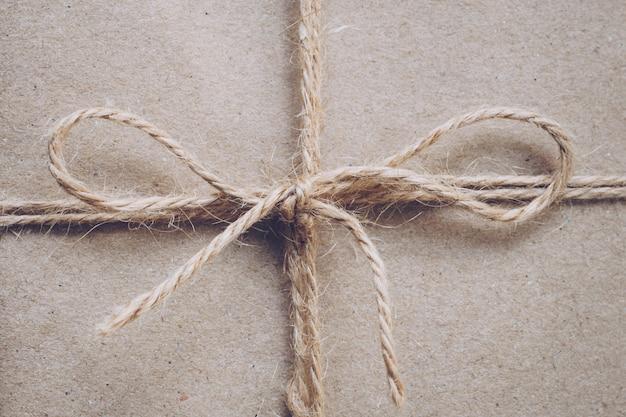 Schnur oder schnur in einem bogen auf kraftpapier textur gebunden