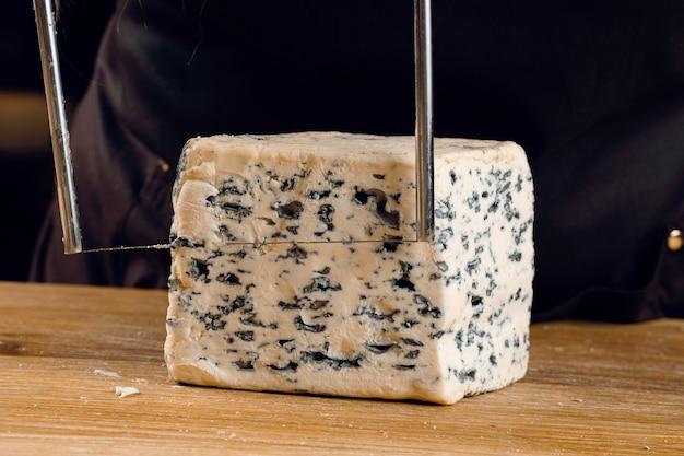 Schnur zum schneiden von blauschimmelkäse. käsemischung auf teller. schneiden von dorblu, gorgonzola, roquefort. französische gourmetküche.