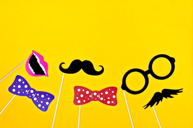 Schnurrbart, krawatte, gläser, roter mund auf hölzernen stöcken gegen hellen gelben hintergrund flach