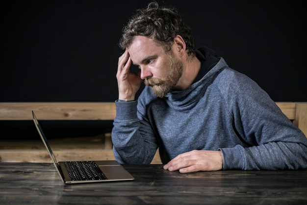Schnurrbarthippie mit einem bart arbeitet am computer