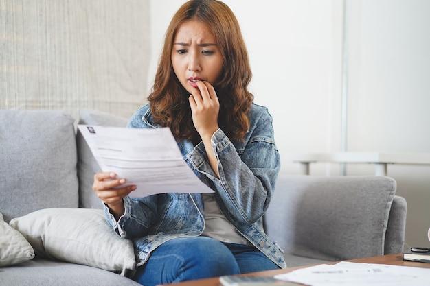 Schock junge asiatische frau, die monatliche rechnungskosten betrachtet