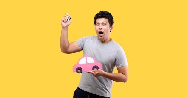 Schock- und überraschungsmann, der papierauto hält und einen autoschlüssel hält