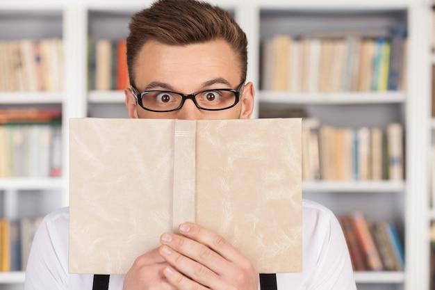 Schockierende geschichte. überraschter junger nerd-mann mit brille, der aus dem buch schaut, während er in der bibliothek steht