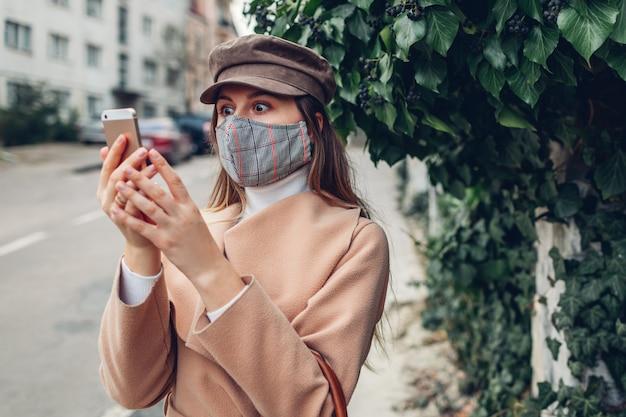 Schockierende nachrichten. frau trägt maske im freien während coronavirus covid-19-pandemie unter verwendung des telefons