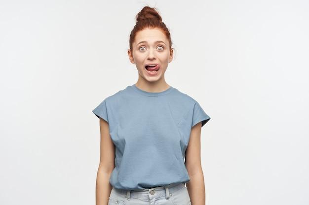 Schockiert aussehende frau, schönes mädchen mit ingwerhaar in einem brötchen gesammelt. trage ein blaues t-shirt und jeans. leck ihre lippe, zeigt zunge. isoliert über weiße wand
