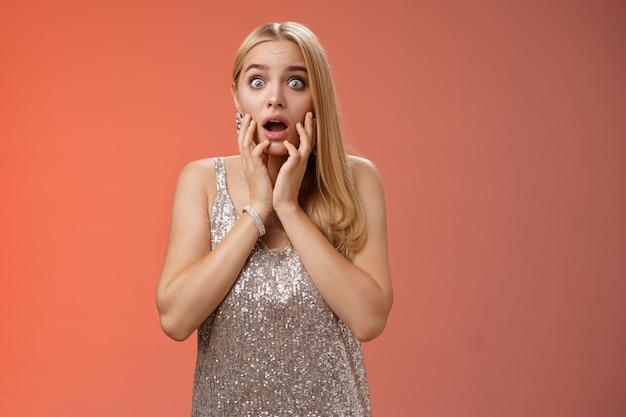 Schockiert besorgt betäubt junge europäische blonde frau in silber dres tropfen kiefer weit aufgerissen augen betäubt sprachlos nach luft schnappen offener mund berührungsgesicht erstaunt, blick verwirrt ratlos, roter hintergrund.