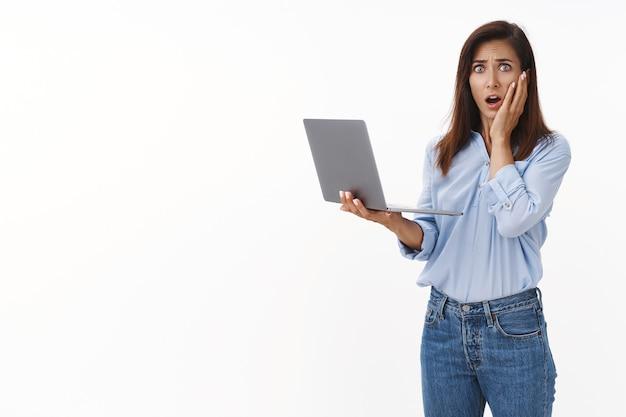 Schockiert besorgte brünette erwachsene frau mit tätowierung, panik, beunruhigter blick von vorne, wange berühren, überfallen, ängstlich nach luft schnappen, laptop halten, datei löschen, schlechte nachrichten erhalten