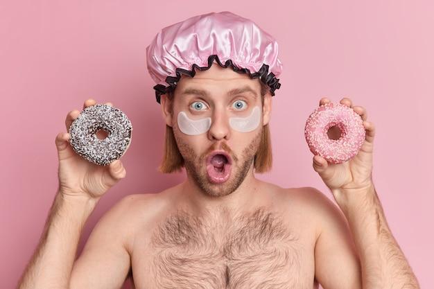 Schockiert blauäugig erwachsener starrt hält mund offen trägt flecken unter den augen für die hautbehandlung trägt badehut hält zwei glasierte donuts steht ohne hemd