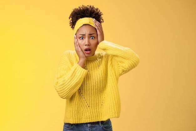 Schockiert erschrocken schüchterne unsichere junge stilvolle afroamerikanische frau panik-touch-gesicht besorgt keuchend offenen mund weiten die augen erschreckt schlechte folgen stehend aufgeregt nervösen gelben hintergrund.