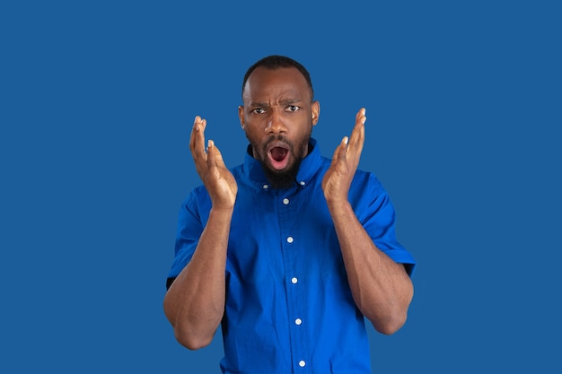 Schockiert, erstaunt. monochromes porträt des jungen afroamerikanischen mannes isoliert auf blauer wand. schönes männliches model. menschliche emotionen, gesichtsausdruck, verkauf, anzeigenkonzept. jugendkultur.