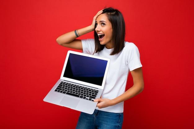 Schockiert erstaunte schöne glückliche überglückliche junge weibliche person mit kurzem, dunkelbraunem haarschnitt Premium Fotos