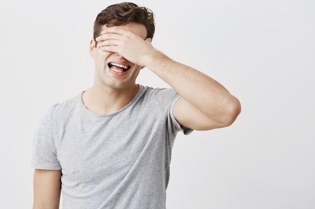 Schockiert gestresster emotionaler junger mann, der sein gesicht hinter seiner hand versteckt, beunruhigt, ratschläge seiner eltern zu hören, die vor dem leeren hintergrund der studiowand isoliert sind. europäischer mann, der müde und verärgert ist