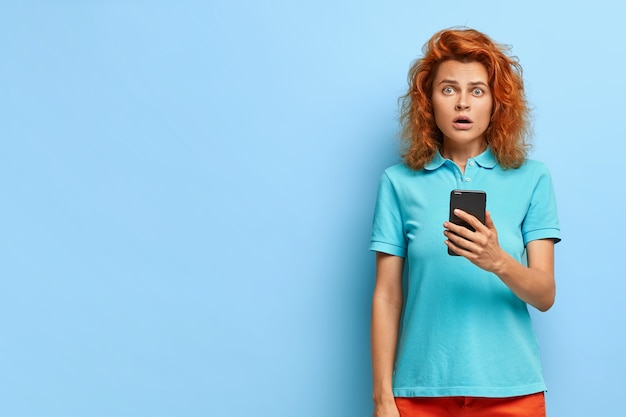 Schockiert schöne europäische frau mit ingwerhaar hat ausdruck beeindruckt, hält modernes handy, bekommt benachrichtigung, in freizeitkleidung gekleidet, modelle über blaue wand mit kopierraum beiseite.