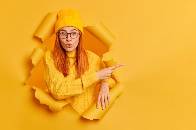 Schockiert schöne europäische frau zeigt auf kopierraum, hat erstaunt ausdruck trägt gelben hut pullover.