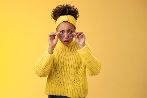 Schockiert sprachlos beeindruckt afroamerikanischer stylischer weiblicher mitarbeiter drop-kiefer-look erstaunt take-off-sonnenbrille weiten die augen kann nicht glauben, verwirrt stehender gelber hintergrund hinterfragte stare-kamera.