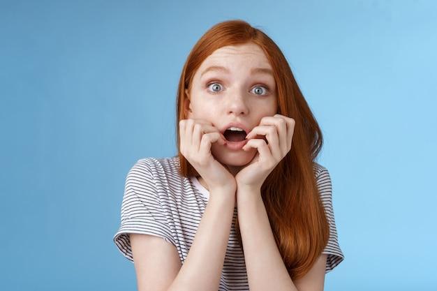 Schockiert sprachlos keuchend junges rothaariges mädchen starrte beeindruckt fassungslos zuschauen wichtigen moment tv-serie beißen finger offen mund schüttelte stehend aufgeregt blauen hintergrund vorwegnehmend.