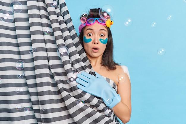 Schockiert überraschte frau trägt lockenwickler kollagenflecken unter den augen auf, unterzieht sich hautpflegeverfahren trägt gummihandschuh duscht im badezimmer