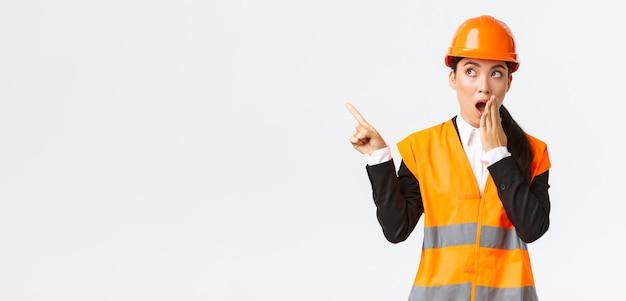 Schockiert und beeindruckt asiatische ingenieurin, bauleiterin in schutzhelm und reflektierender jacke, keuchender zeigefinger obere linke ecke erstaunt, etwas interessantes herausgefunden