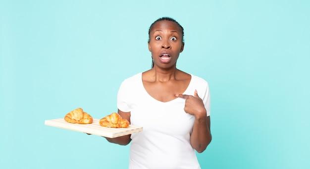 Schockiert und überrascht mit weit geöffnetem mund aussehend, auf sich selbst zeigend und ein croissant-tablett haltend