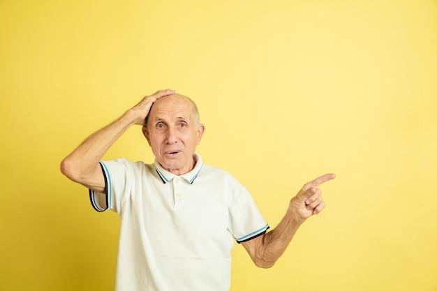 Schockiert und zur seite zeigend. porträt des kaukasischen älteren mannes auf gelbem studiohintergrund. schönes männliches emotionales modell. konzept der menschlichen emotionen, gesichtsausdruck, verkauf, wohlbefinden, anzeige. copyspace.