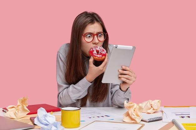 Schockiert unzufrieden attraktive frau konzentriert auf dem bildschirm des touchpads, liest schockierende nachrichten im internet, trägt transparente brille, hält moderne tablet