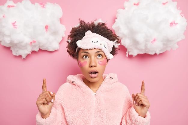 Schockiert wunderte sich eine afroamerikanische frau mit polstern unter den augen nach oben, beeindruckt von einer unglaublichen sache, die den kiefer fallen lässt. sie trägt nachtwäsche mit verbundenen augen auf der stirn und zeigt etwas auf weißen wolken