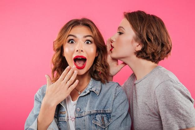 Schockiert zwei freundinnen klatschen.