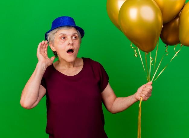 Schockierte ältere frau, die partyhut trägt, hält heliumballons, die hand hinter ohr halten, das seite auf grün betrachtet