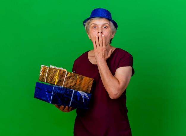 Schockierte ältere frau, die partyhut trägt, legt hand auf mund, der geschenkboxen auf grün hält