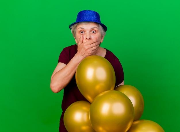 Schockierte ältere frau, die partyhut trägt, setzt hand auf mund, der mit heliumballons auf grün steht
