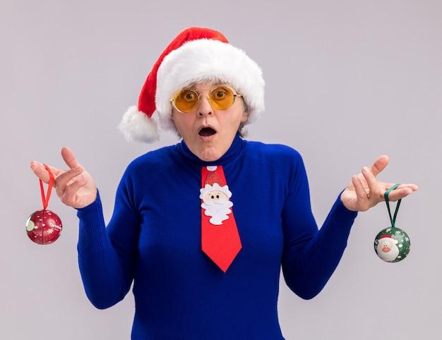 Schockierte ältere frau in sonnenbrille mit weihnachtsmütze und weihnachtsmann-krawatte, die glaskugelverzierungen isoliert auf weißer wand mit kopienraum hält