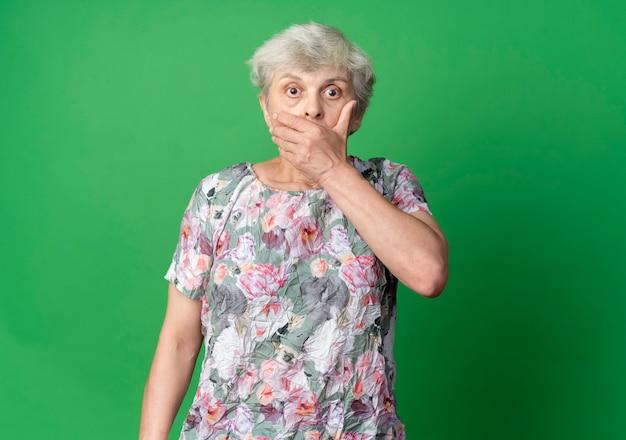 Schockierte ältere frau legt hand auf mund, der lokal auf grüner wand schaut