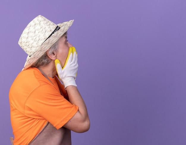 Schockierte ältere gärtnerin, die gartenhut und handschuhe trägt, legt hände auf mund und schaut zur seite auf purpur