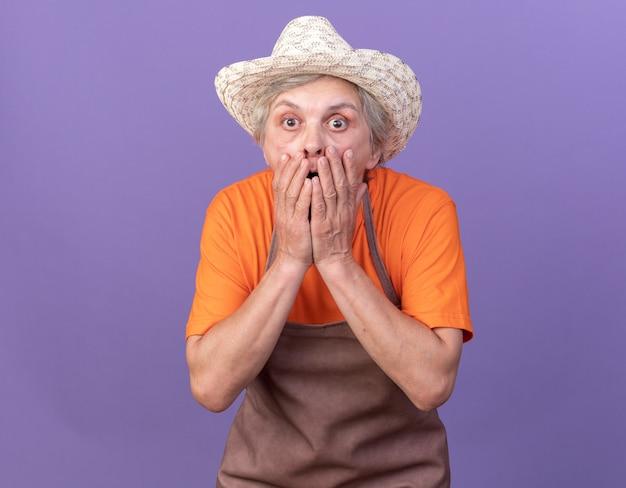 Schockierte ältere gärtnerin mit gartenhut legt die hände auf den mund, isoliert auf lila wand mit kopierraum